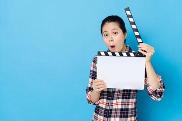 woman playing clapboard looking at camera