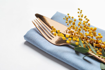 Beautifully decorated cutlery for Easter table setting with mimosa on white background
