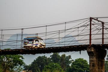 mini car transport driving through old wooden bridge Vang Vieng Laos
