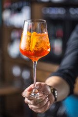 Aperol spritz drink. Bartender hand holding glass with  Aperol Spritz drink.