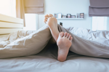 Close up of  barefoot,Feet and stretch lazily on the bed after waking up