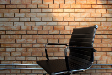 Unused black leather office chair in front of brick wall background
