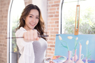 Asian woman paints picture on canvas with oil paints. Woman painting picture with attractive smiling.