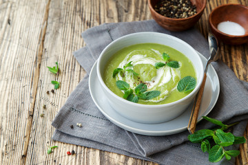Green peas and broccoli soup . Wooden background, Scandinavian style