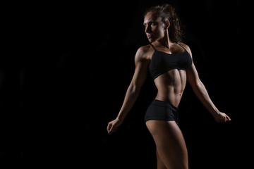 Fit woman posing on black background