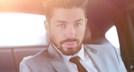 Businessman drinking coffee in the back seat of a car