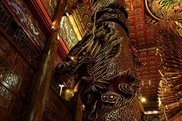 High pillars carved into dragons. Made from big tree. Chinese Temple
