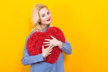 Wall Mural - Blonde woman hugging big red flower heart