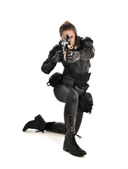 full length portrait of female wearing black  tactical armour, crouching pose holding a weapon, isolated on white studio background.