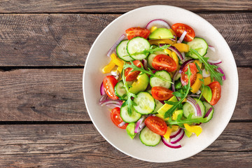 Healthy vegetarian dish, vegetable salad with fresh tomato, cucumber, bell pepper, red onion, avocado and arugula