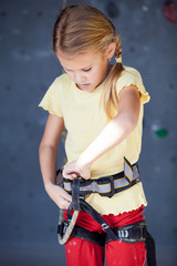 little girl standing near a climbing  rock wall indoor.
