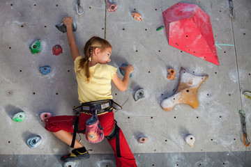little girl climbing a rock wall indoor.