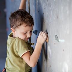 little boy climbing a rock wall indoor.