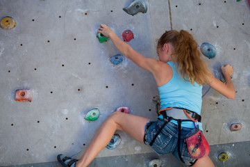 Teen girl climbing a rock wall indoor.