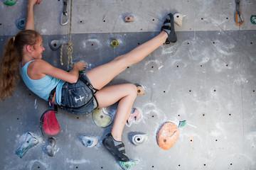 Teen girl climbing a rock wall indoor.