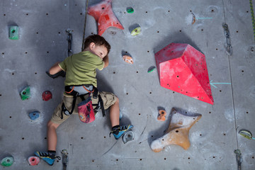 little boy climbing a rock wall indoor.