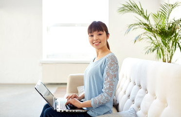 happy asian woman with laptop computer at office