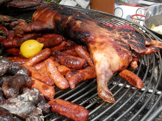 Smoked and cooked meats and sausages on large round barbeque