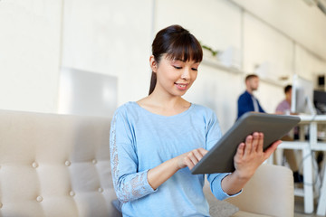 happy asian woman with tablet pc working at office