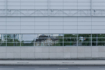WALL - The reflection of the city in the glass windows of an industrial building