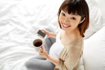 happy pregnant woman with cup of tea in bed