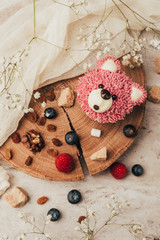 top view of delicious muffin in shape of bear with berries on wooden board