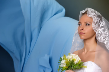 a bride with a veil on her head and flowers in her hands, a studio photo, a wedding