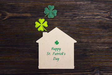 St.Patrick's day greeting message with home symbol and clover  leaves on wooden background.