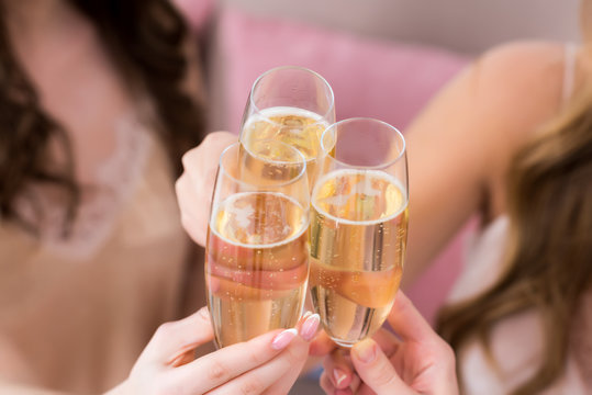 cropped shot of young women clinking glasses of champagne