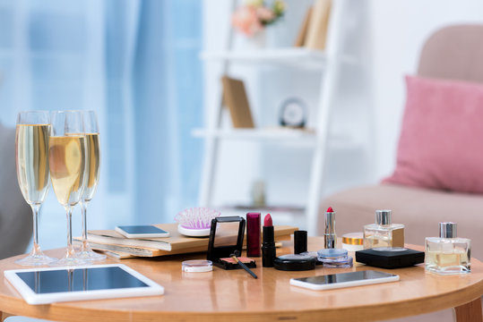 close-up view of gadgets, glasses of champagne and various cosmetics on table