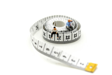 Miniature people : people sitting with measuring tape of the tailor,heathcare concept.