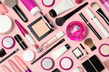 Set of makeup cosmetics, brushes, concealer and other essentials on pink background