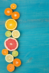 food background with sliced citrus fruits on a blue background vertical