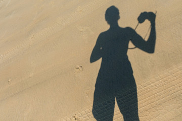 Photographer's shadow on the sand. Yound man doing the photo of his shadow on the sand.