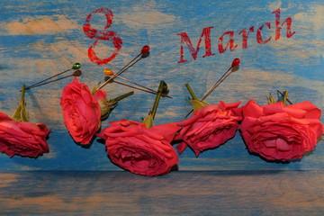 поздравления с 8 марта, розовая роза лежит на фоне синих деревянных досок