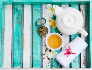 Green tea in white cup and teapot, welcome spa set. Wooden colorful tray. Top view. Copy space.