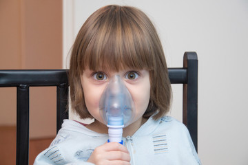 Beautiful girl using the inhalation mask