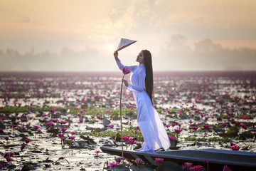 Portrait woman wearing Ao Dai traditional dress of Vietnamese standing on the boat at lake.