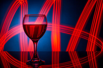A glass of red wine closeup on the background of bright lights..