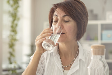 Middle aged woman drinking water