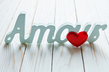 love, love. red heart and the word amour on a white wooden background