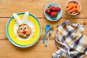 Easter breakfast for kids. Easter bunny shaped pancake with fruits on yellow plate. Colorful meal for children on wooden table, top view