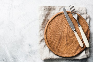 Vintage silverware and wooden board on grey concrete background. Top view, copy space for text