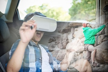 Composite image of boy using virtual reality headset