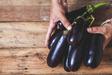 Hands take few eggplants on wooden boards