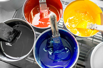Four open buckets with CMYK paints at the printing manufacturing