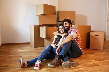 Young couple moving into a  new home.Sitting on floor in empty apartment .Real estate concept.