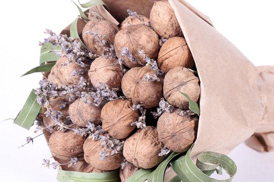 букет из грецких орехов  лаванды и цитрусовых лежит на белом фоне