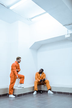 multiethnic prisoners in light modern prison cell
