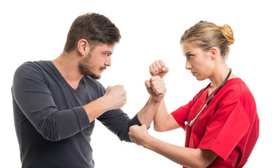 Lady doctor and male patient in fighting position.